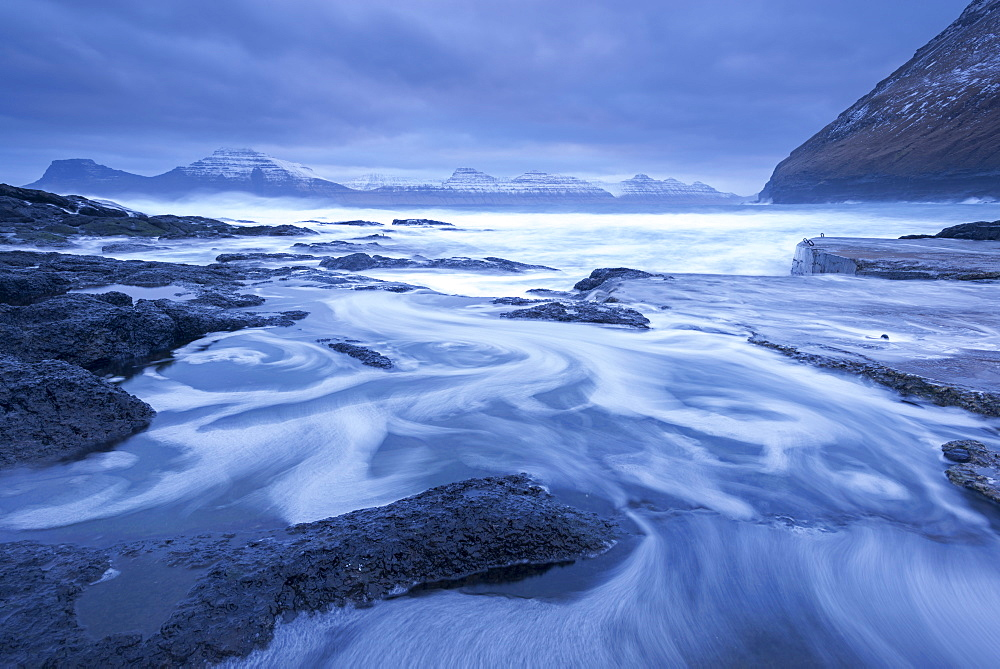 Atlantic waves swirl and crash over the rocky shores of Gjogv on the island of Eysturoy in winter, Faroe Islands, Denmark, Europe