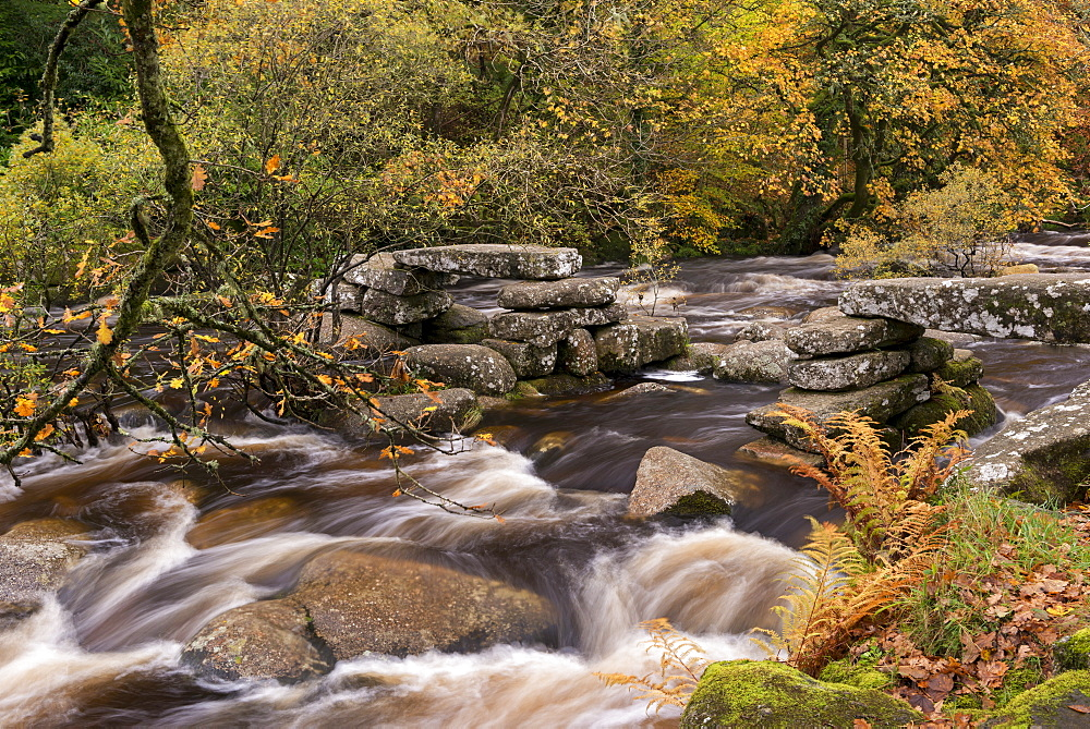 River Dart tumbling past an ancient stone clapper bridge at Dartmeet, Dartmoor National Park, Devon, England, United Kingdom, Europe