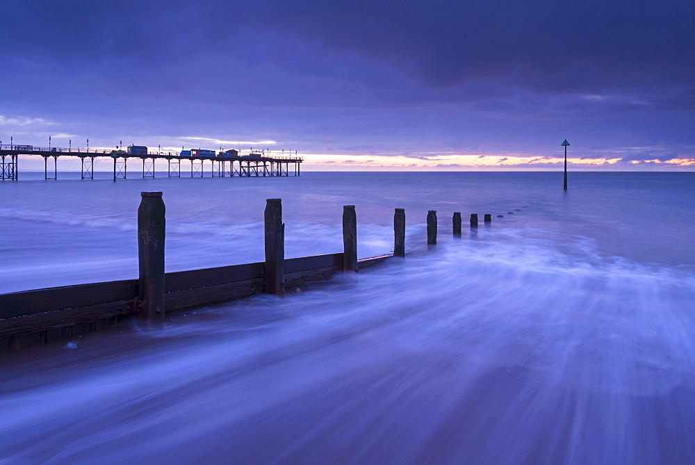 Waves rush over the beach at Teignmouth at dawn in winter, Devon, England, United Kingdom, Europe