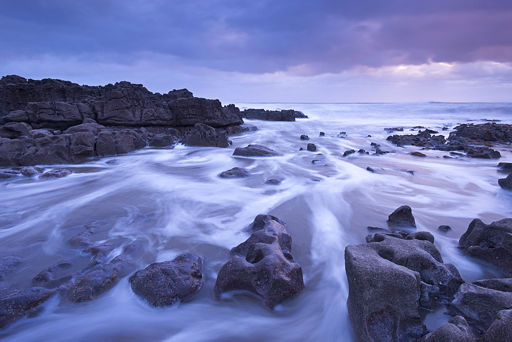 Sunset off the rugged coastline of Porthcawl on the Glamorgan coast in winter, Wales, United Kingdom, Europe