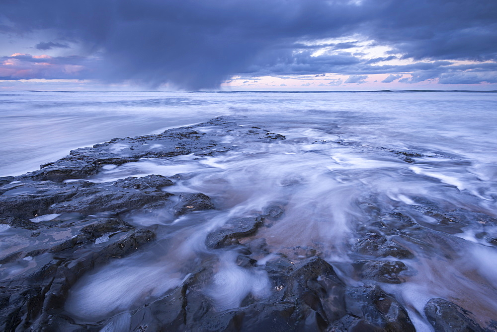 A winter storm passes over the Farne Islands, photographed from the basalt shore near Bamburgh Beach, Northumberland, England, United Kingdom, Europe