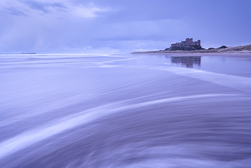 Waves wash over the beach next to Bamburgh Castle on a stormy winter evening, Northumberland, England, United Kingdom, Europe