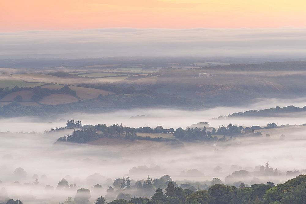 Mist floats over rolling countryside below Castle Drogo at dawn, Dartmoor, Devon, England, United Kingdom, Europe
