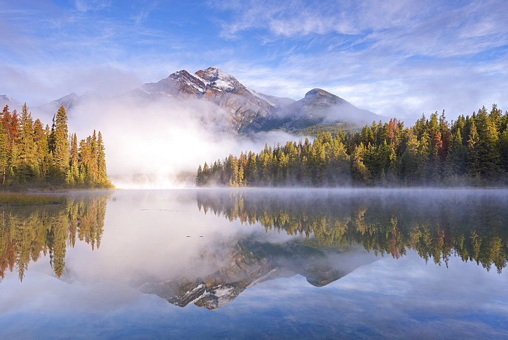 Mist obscures Pyramid Mountain, reflected in Pyramid Lake in the Canadian Rockies, Jasper National Park, Alberta, Canada. Autumn