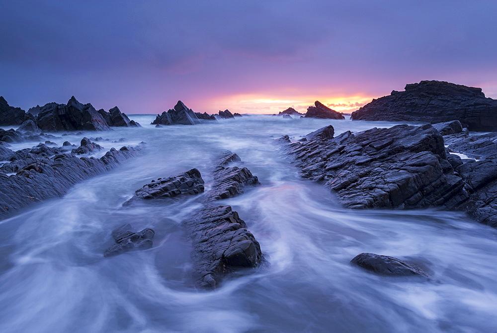 Sunset over the dramatic coastline of Hartland Quay, North Devon, England. Spring (April) 2016.