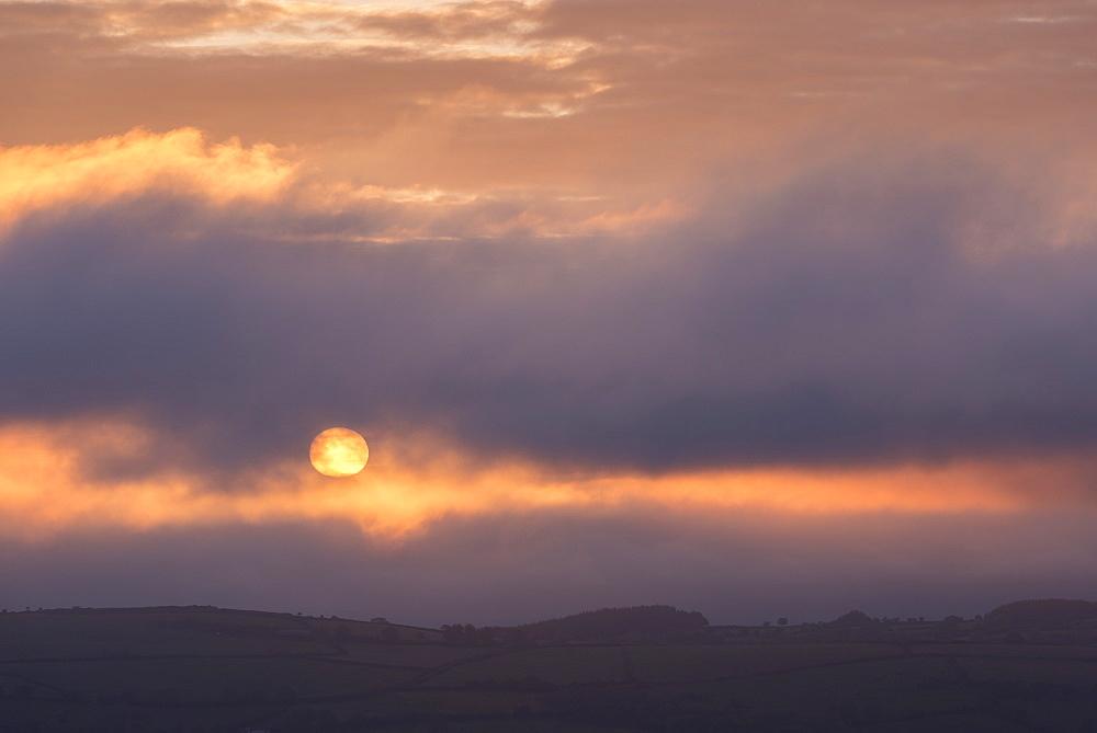 Atmospheric sunrise over Dartmoor National Park, Devon, England. Spring (May) 2015.