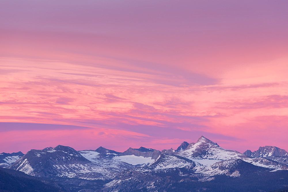 Colourful sunset skies above the snow dusted mountains of Yosemite National Park, California, USA. Spring (June) 2016.