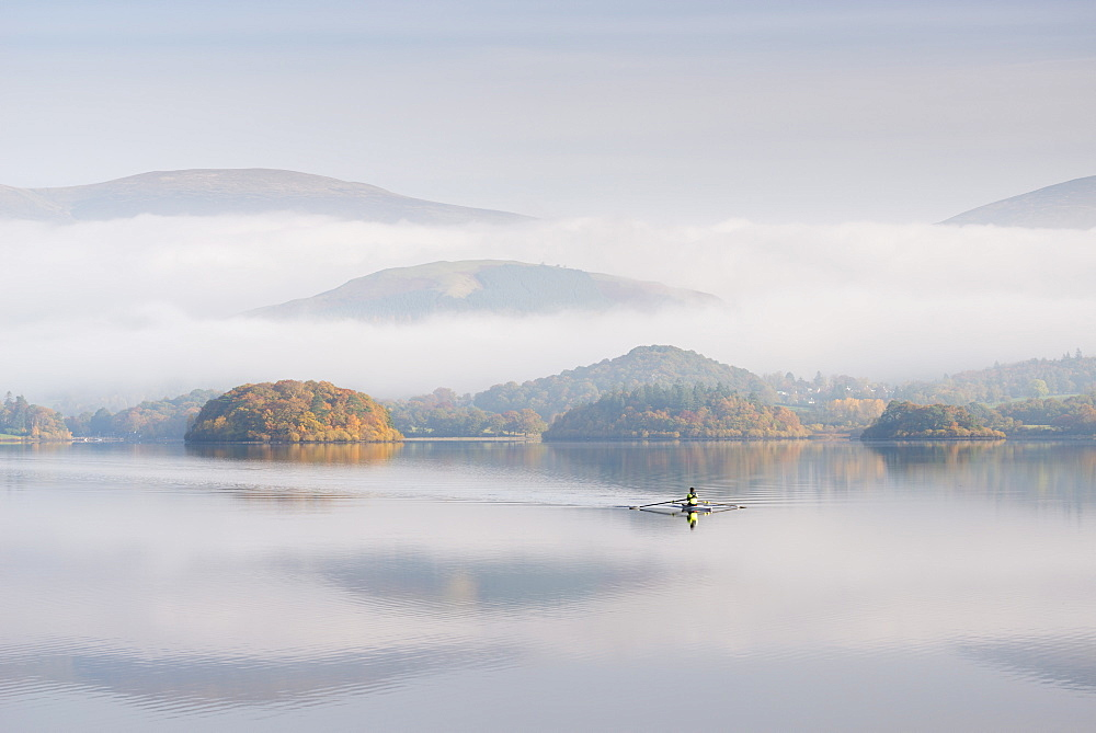 Single sculler rowing across a misty Derwent Water at dawn, Lake District, Cumbria, England. Autumn (October) 2016.