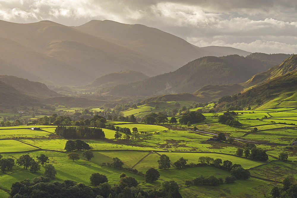Early morning sunlight illuminates the rolling countryside near Keswick in the Lake District, Cumbria, England. Autumn (Septembe
