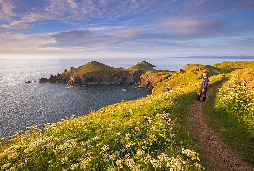 Man appreciating the beautiful coastal view at The Rumps, North Cornwall, England. Summer (June) 2015.