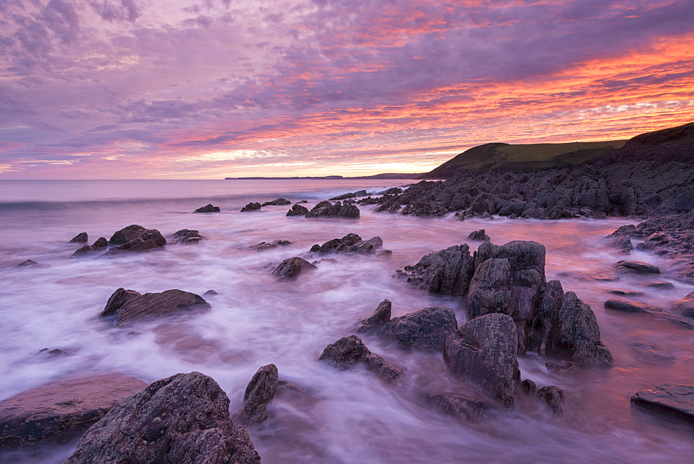 Colourful sunset over the rocky shores of Manorbier Beach, Pembrokeshire, Wales, United Kingdom, Europe