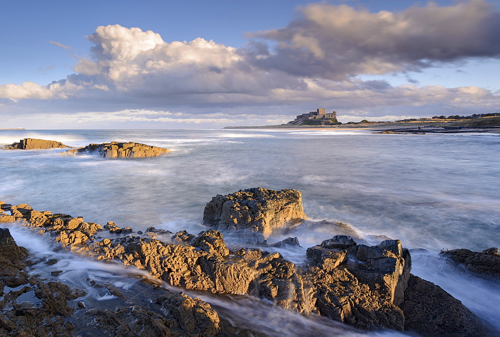 Looking across rocky ledges to Bamburgh Castle, Northumberland, England, United Kingdom, Europe - 799-3447