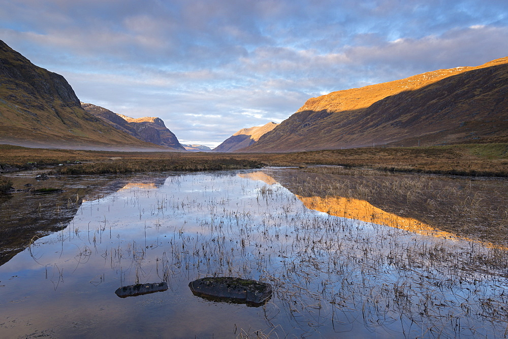 Sunlit mountains of Glencoe, reflected in the still waters of Lochan na Fola, Highlands, Scotland, United Kingdom, Europe