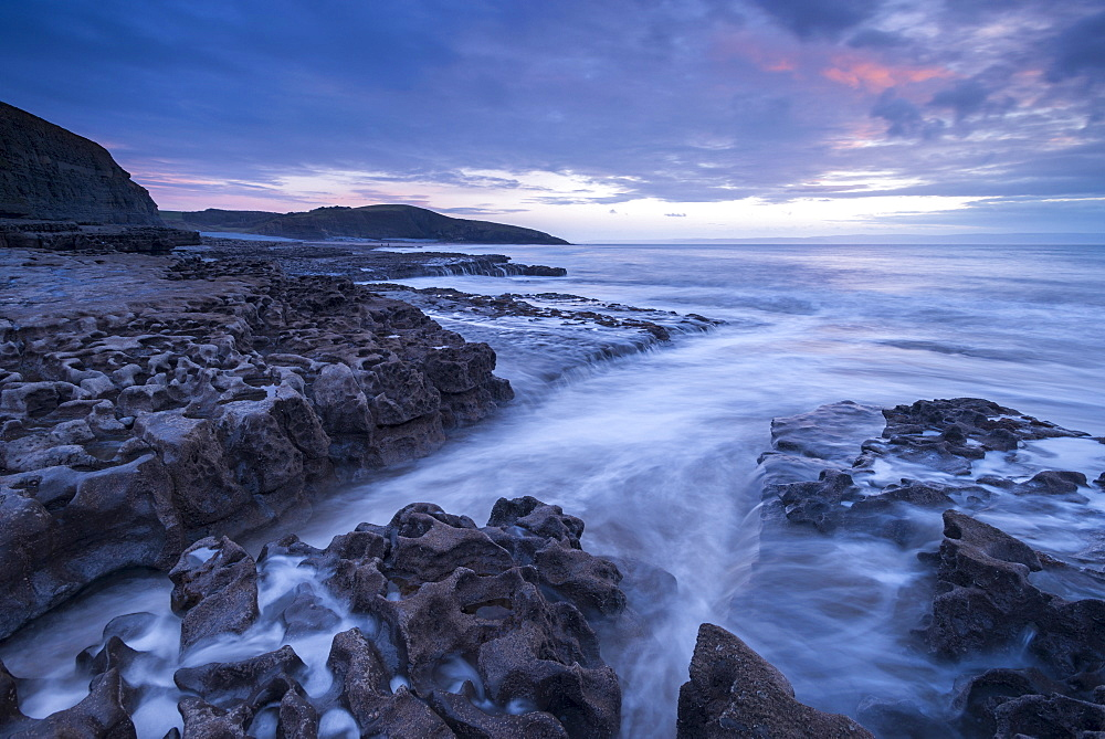 Waves surge over the rocky ledges of Dunraven Bay on the Glamorgan Heritage Coast in winter, Southerndown, Wales, United Kingdom, Europe
