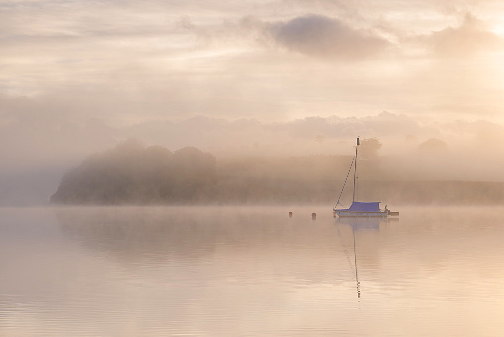 Sailing boat moored on a misty Wimbleball Lake at dawn, Exmoor National Park, Somerset, England. Spring (May) 2017.