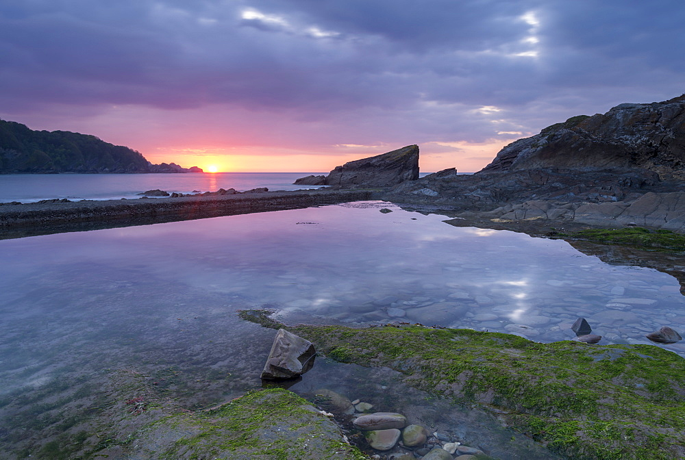 Sunset reflected in a rock pool at Combe Martin on the Exmoor coast, North Devon, England, United Kingdom, Europe
