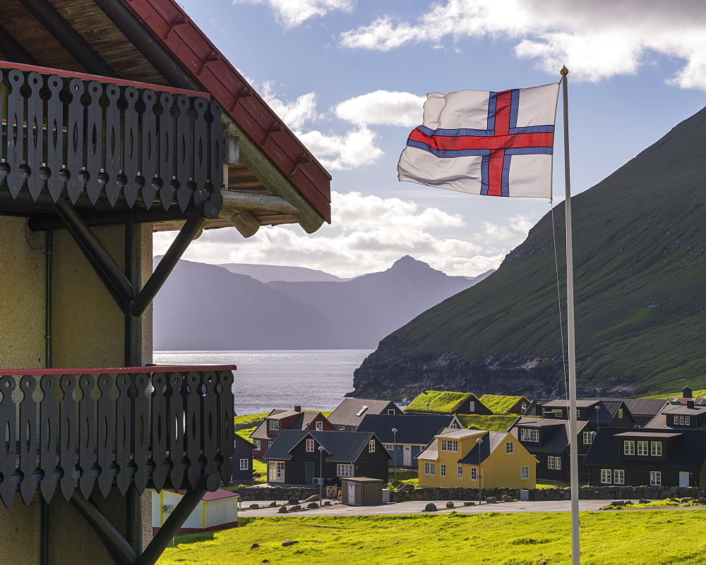 Faroese flag flying in the breeze above the village of Gjógv in the Faroe Islands, Denmark. Summer (June) 2017.