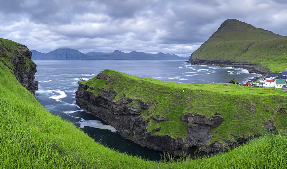 Cliff top view over the gorge at Gjogv towards the island of Kalsoy, Eysturoy, Faroe Islands, Denmark, Europe