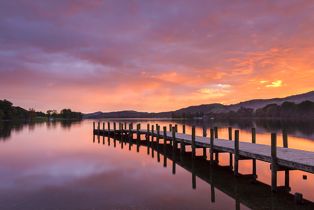 Spectacular colourful sunset above one of Lake Coniston's wooden jetties, Lake District, UNESCO World Heritage Site, Cumbria, England, United Kingdom, Europe