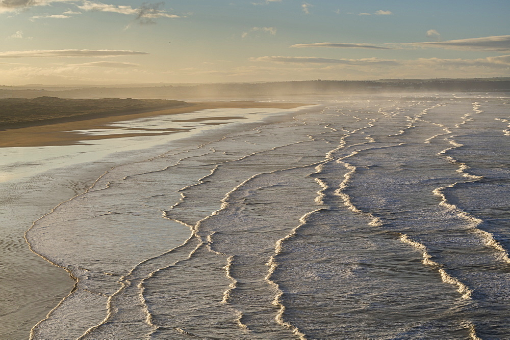 Breaking waves roll towards Saunton Sands at dawn in winter in North Devon, England, United Kingdom, Europe