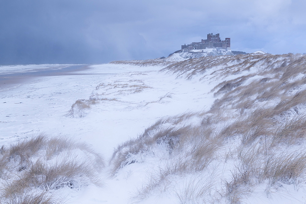 Snow covered beach and sand dunes by Bamburgh Castle in winter, Northumberland, England, United Kingdom, Europe