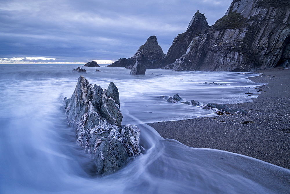 Waves surge over the dramatic rocky beach at Westcombe in the South Hams in winter, Devon, England, United Kingdom, Europe