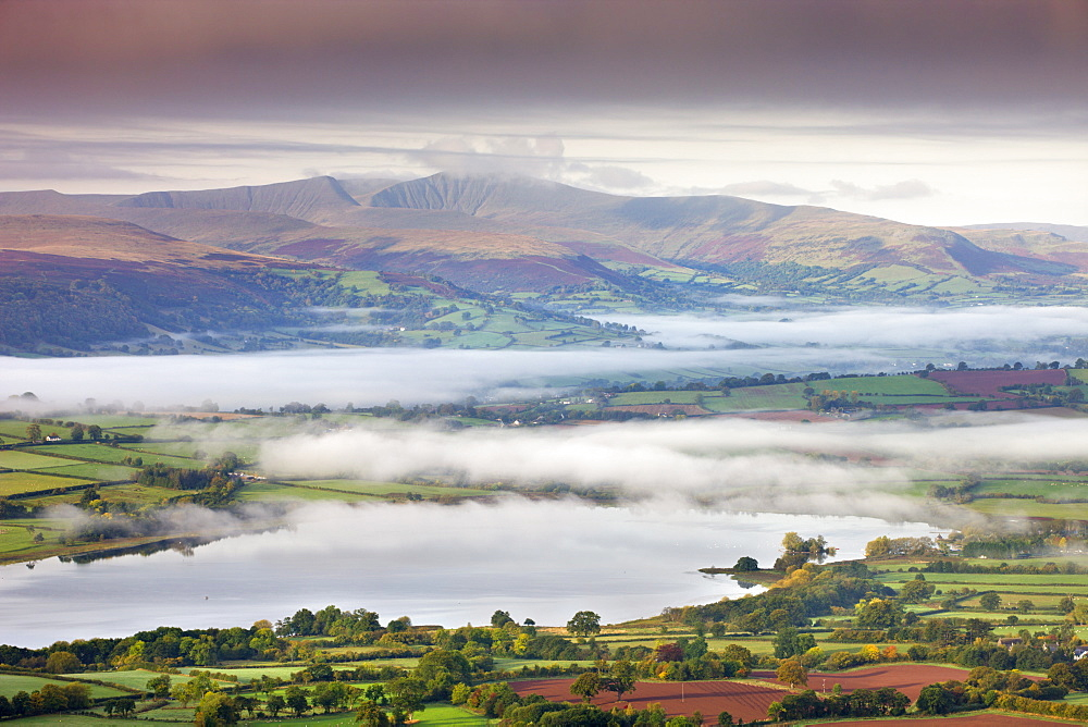 Pen Y Fan rises above a mist shrouded landscape near Llangorse Lake, Brecon Beacons National Park, Powys, Wales, United Kingdom, Europe
