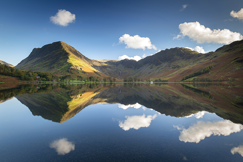 Perfect reflections on a tranquil Lake Buttermere in the Lake District, Cumbria, England. Autumn (October) 2018.