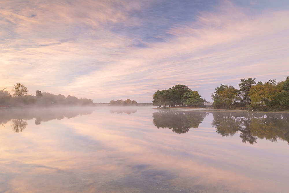 Hatchet Pond reflecting a beautiful pink misty sunrise, Beaulieu, New Forest, England. Autumn (November) 2018.