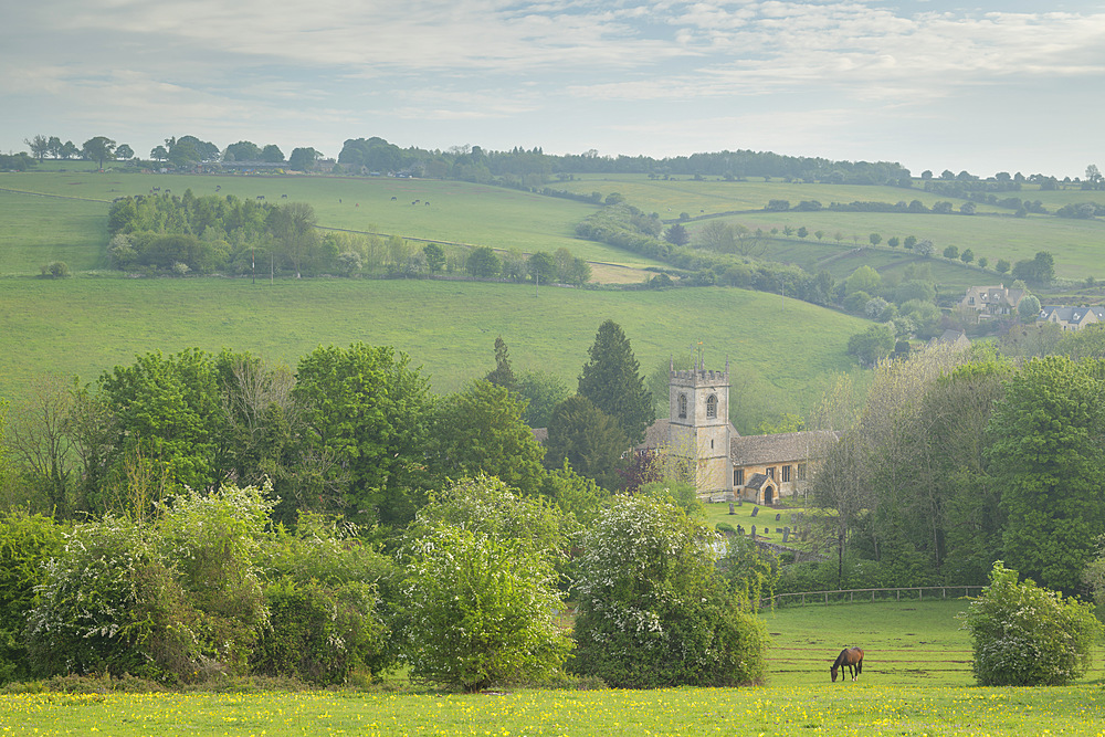 Rural church in beautiful Cotswolds countryside on a hazy spring morning, Naunton, Gloucestershire, England. Spring (May) 2019.