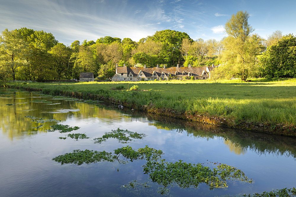 Arlington Row cottages across the River Coln in the Cotswolds village of Bibury, Gloucestershire, England, United Kingdom, Europe