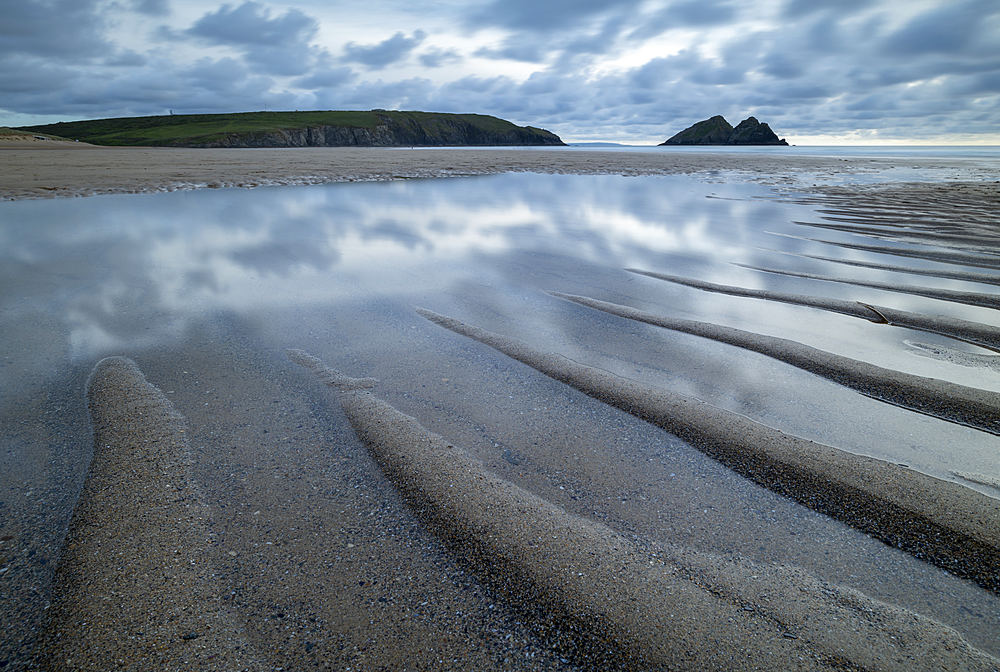 Tidal pools on the sandy beach at Holywell Bay, Cornwall, England. Summer (June) 2019.