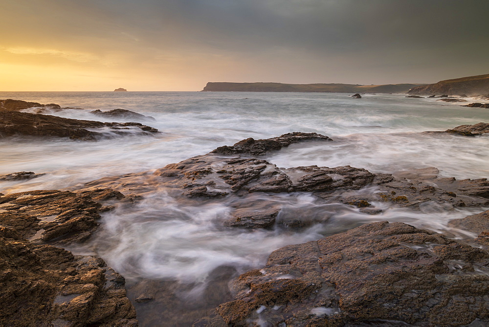 Waves swirl over rocky ledges at sunset on the North Cornwall coast, England. Summer (July) 2019. - 799-3842
