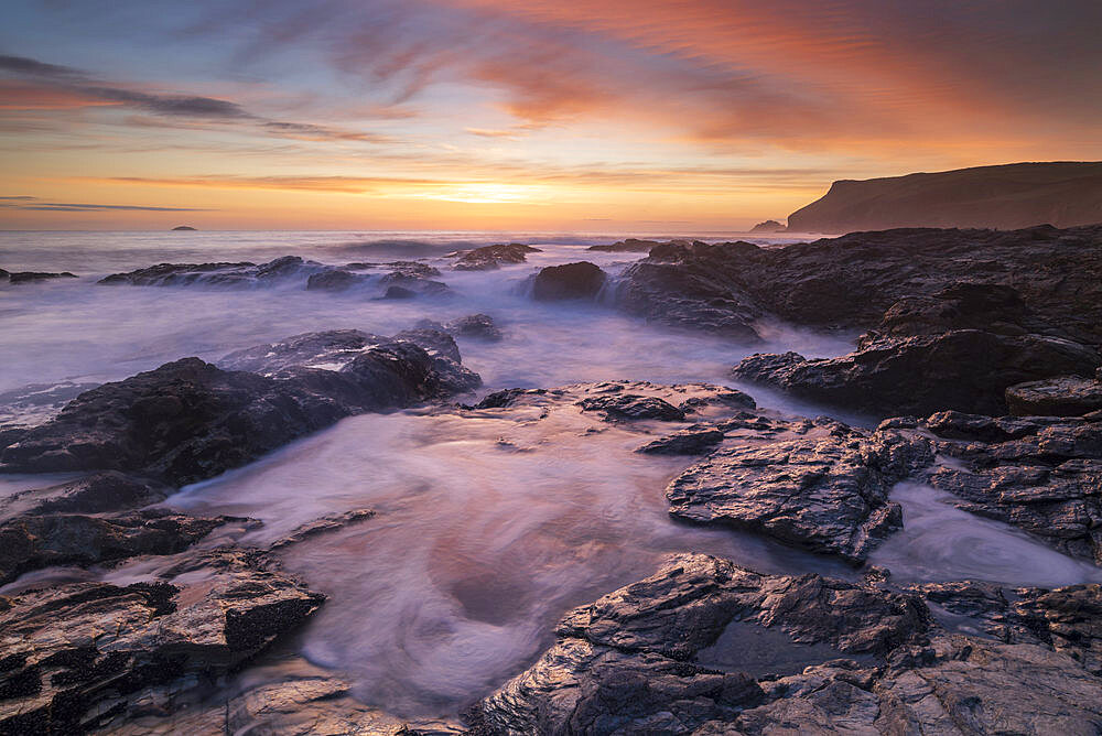 Colourful Cornish sunset above rocky ledges near Polzeath, Cornwall, England, United Kingdom, Europe