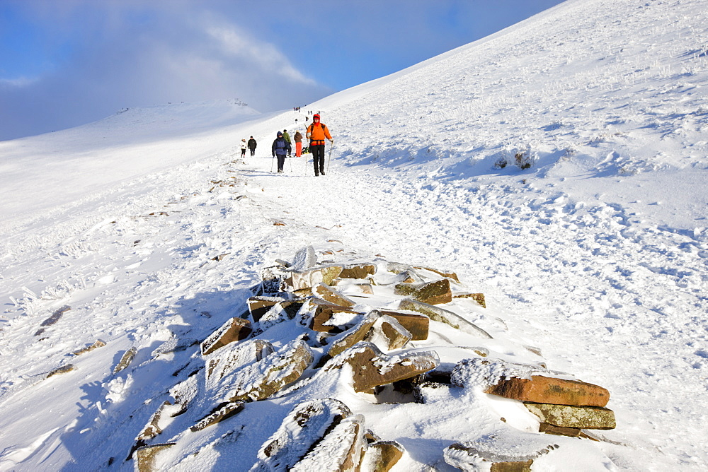 Walkers descend the snowy footpath from Corn Du and Pen Y Fan mountains in winter, Brecon Beacons National Park, Powys, Wales, United Kingdom, Europe