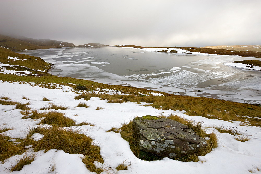 Melting snow on the moorland above an ice covered Llyn y Fan Fawr in winter, Black Mountain, Brecon Beacons National Park, Wales, United Kingdom, Europe