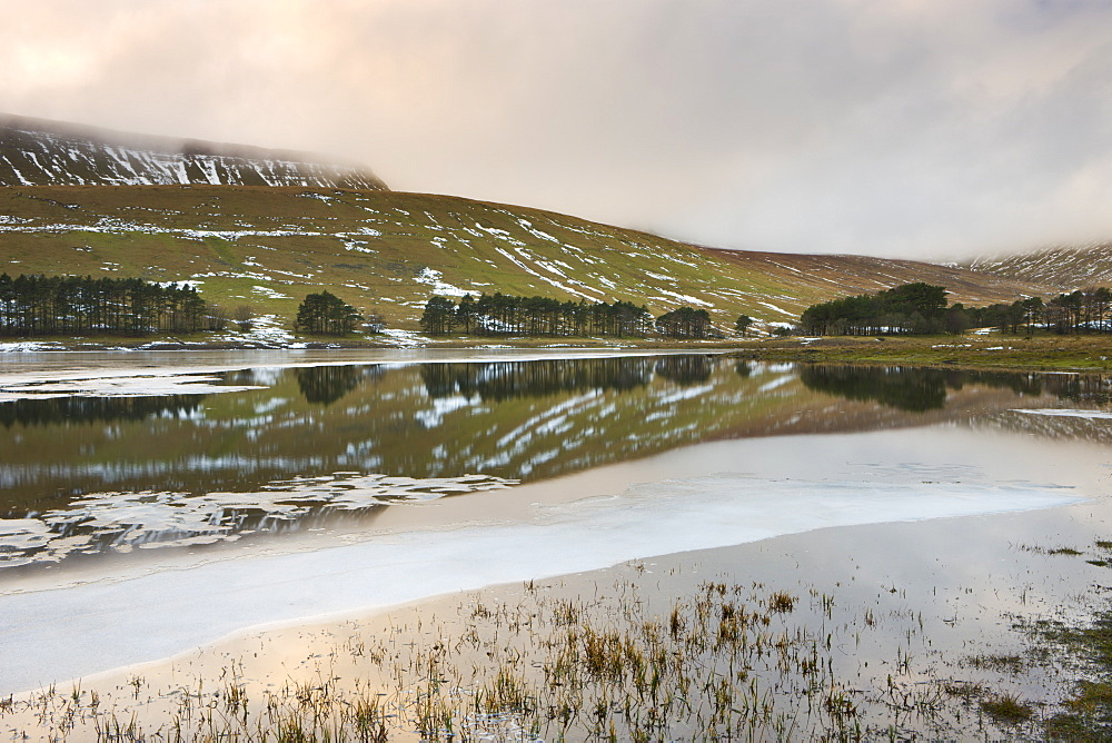 Sunset reflected in the icy waters of the Upper Neuadd Reservoir, with Graig Fan Ddu escarpment in the background in winter, Brecon Beacons National Park, Powys, Wales, United Kingdom, Europe