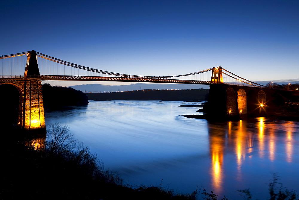 Evening illuminations on the Menai Bridge spanning the Menai Strait, Anglesey, North Wales, Wales, United Kingdom, Europe