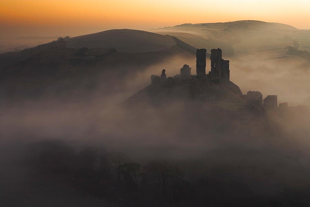 A sea of mist swirls around the base of Corfe Castle at dawn, Corfe, Dorset, England, United Kingdom, Europe