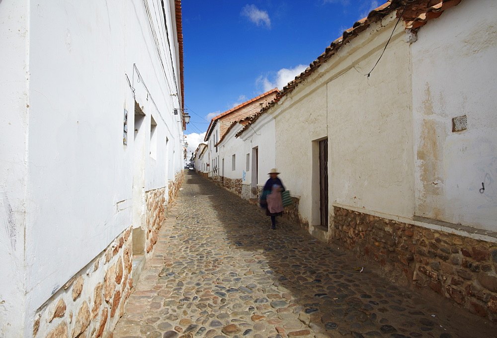 Woman walking along alleyway, Sucre, UNESCO World Heritage Site, Bolivia, South America