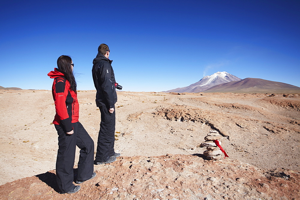 Couple looking at volcano on Altiplano, Potosi Department, Bolivia, South America