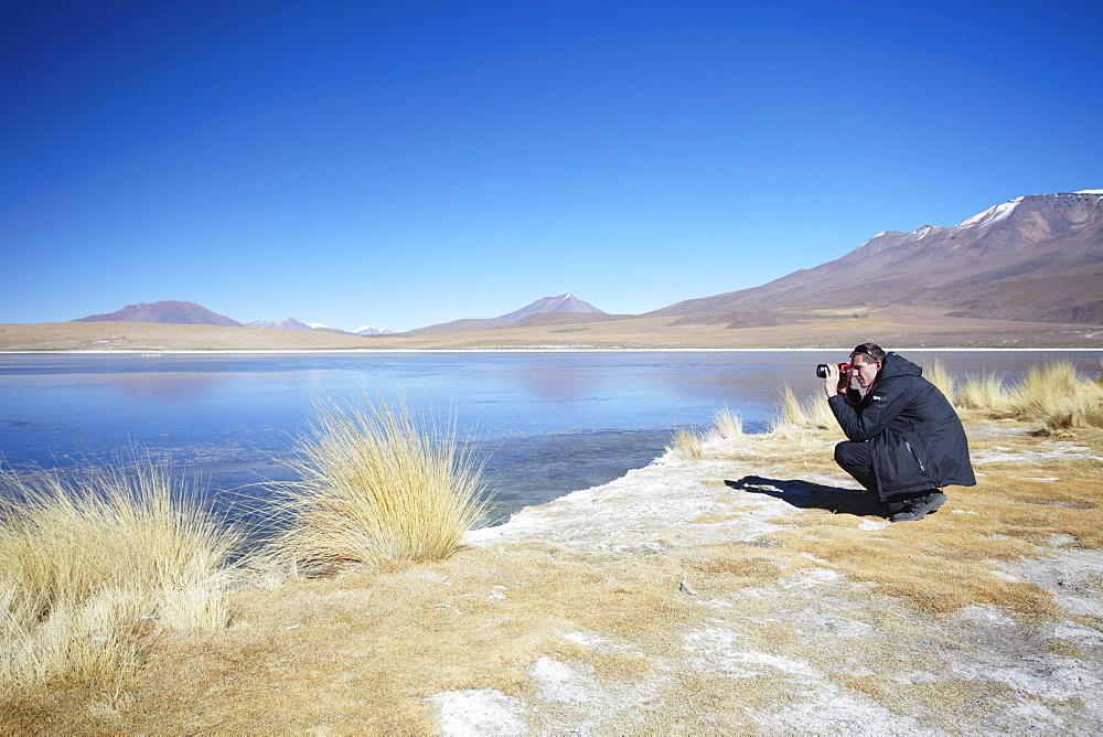 Man taking photos at Laguna Canapa on Altiplano, Potosi Department, Bolivia, South America