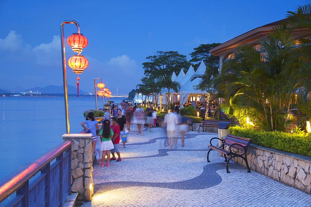 People walking along promenade at dusk, Discovery Bay, Lantau, Hong Kong, China, Asia