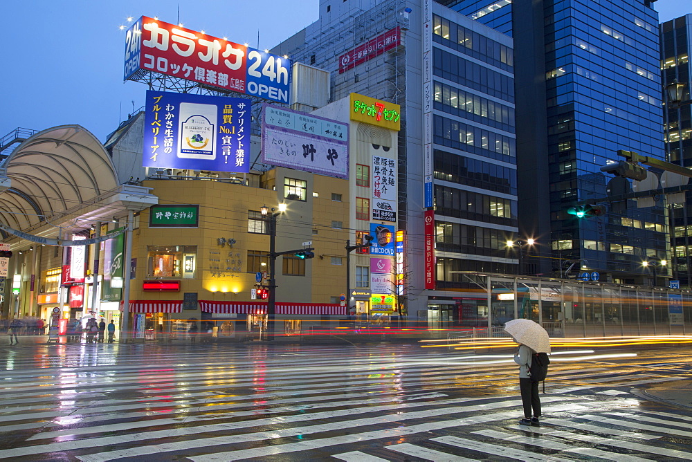 Person waiting to cross street at Hondori shopping arcade at dusk, Hiroshima, Hiroshima Prefecture, Japan, Asia