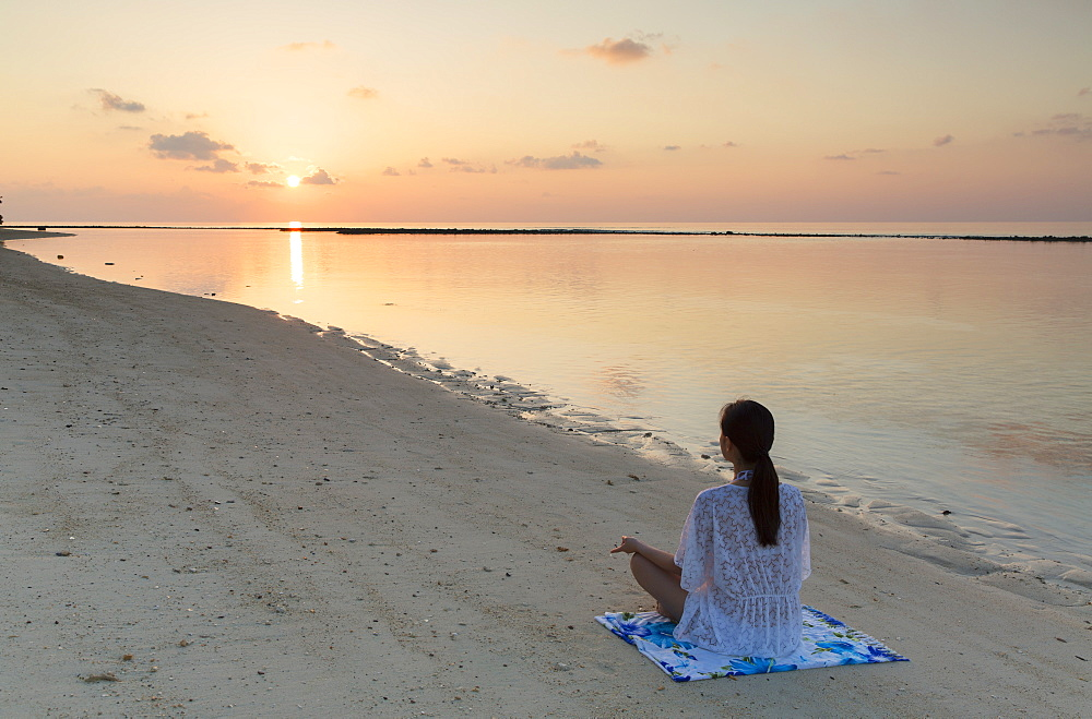 Woman practising yoga at sunrise, Rasdhoo Island, Northern Ari Atoll, Maldives, Indian Ocean, Asia