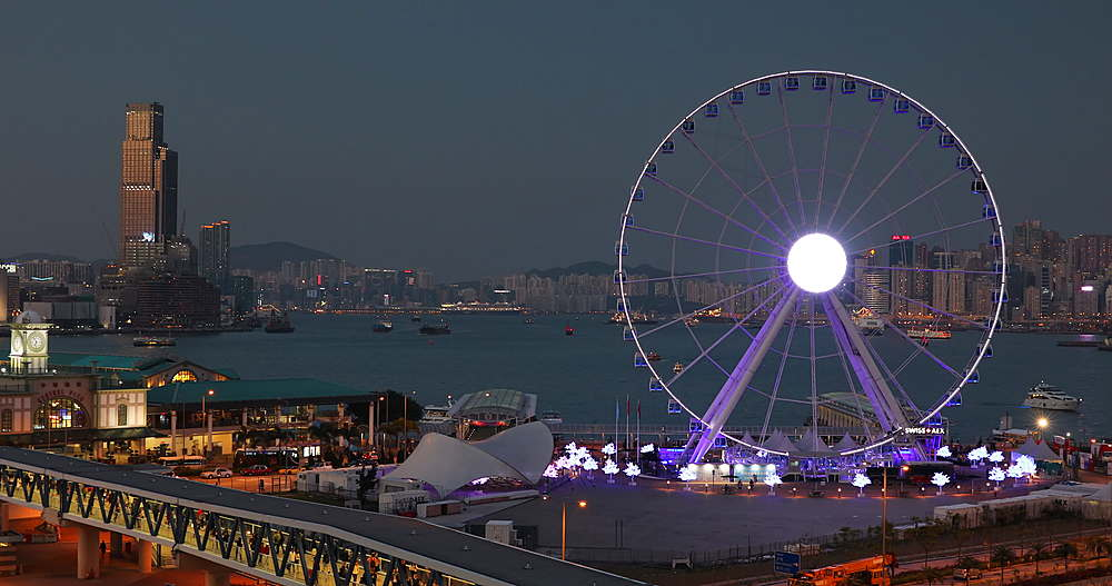 View of Star Ferry pier and Ferris wheel at dusk, Hong Kong, China, Asia