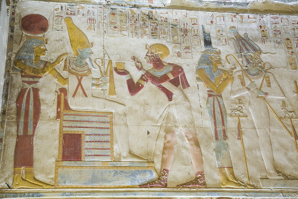 Pharaoh Seti I in center making an offering to the seated God Osiris, Temple of Seti I, Abydos, Egypt, North Africa, Africa