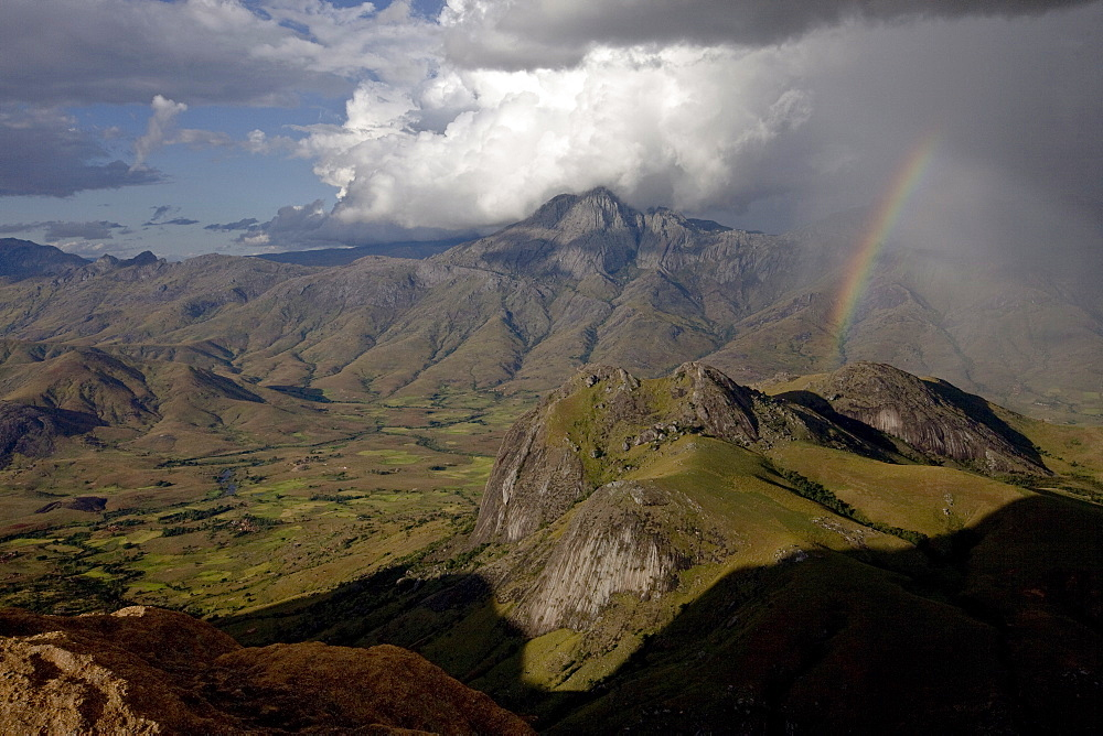 A rainbow appears looking east across the granite mountains of the Andringitra National Park, as a squall of rain blows in from the Indian Ocean, Southern Madagascar, Africa