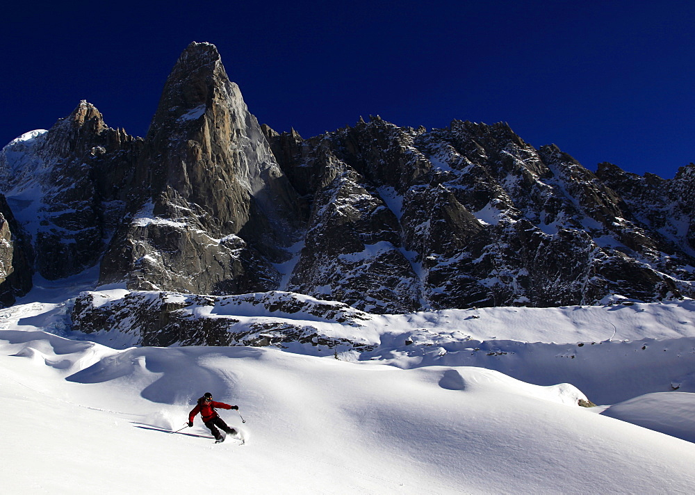 A skier enjoying perfect powder snow on the celebrated Pas de Chevre off-piste run, with the Dru in the background, Chamonix Valley, Chamonix, Haute Savoie, French Alps, France, Europe