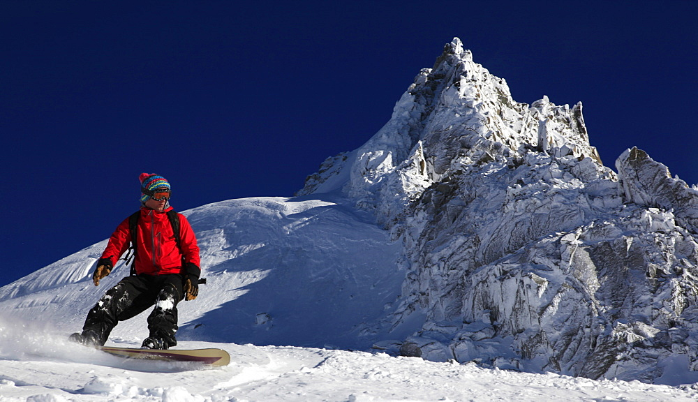 A snowboarder riding powder snow off the top of the famous Grand Montets ski area, high above Argentiere, Chamonix Valley, Haute Savoie, French Alps, France, Europe